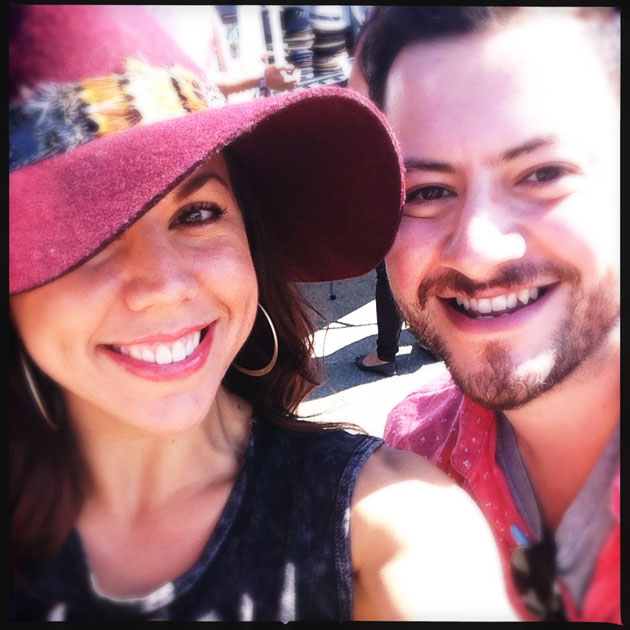 Molli Sullivan wears a large fuschia hat and takes a happy selfie with her partner