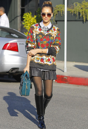 Jessica Alba wearing sunglasses, a sweater and a leather skirt.