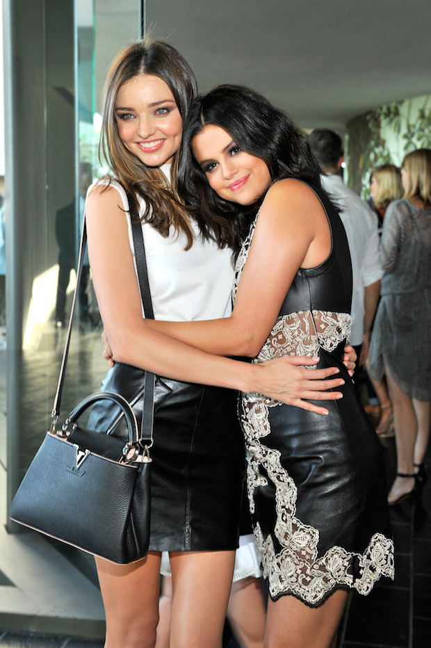 Miranda Kerr and Selena Gomez cuddle at Louis Vuitton show