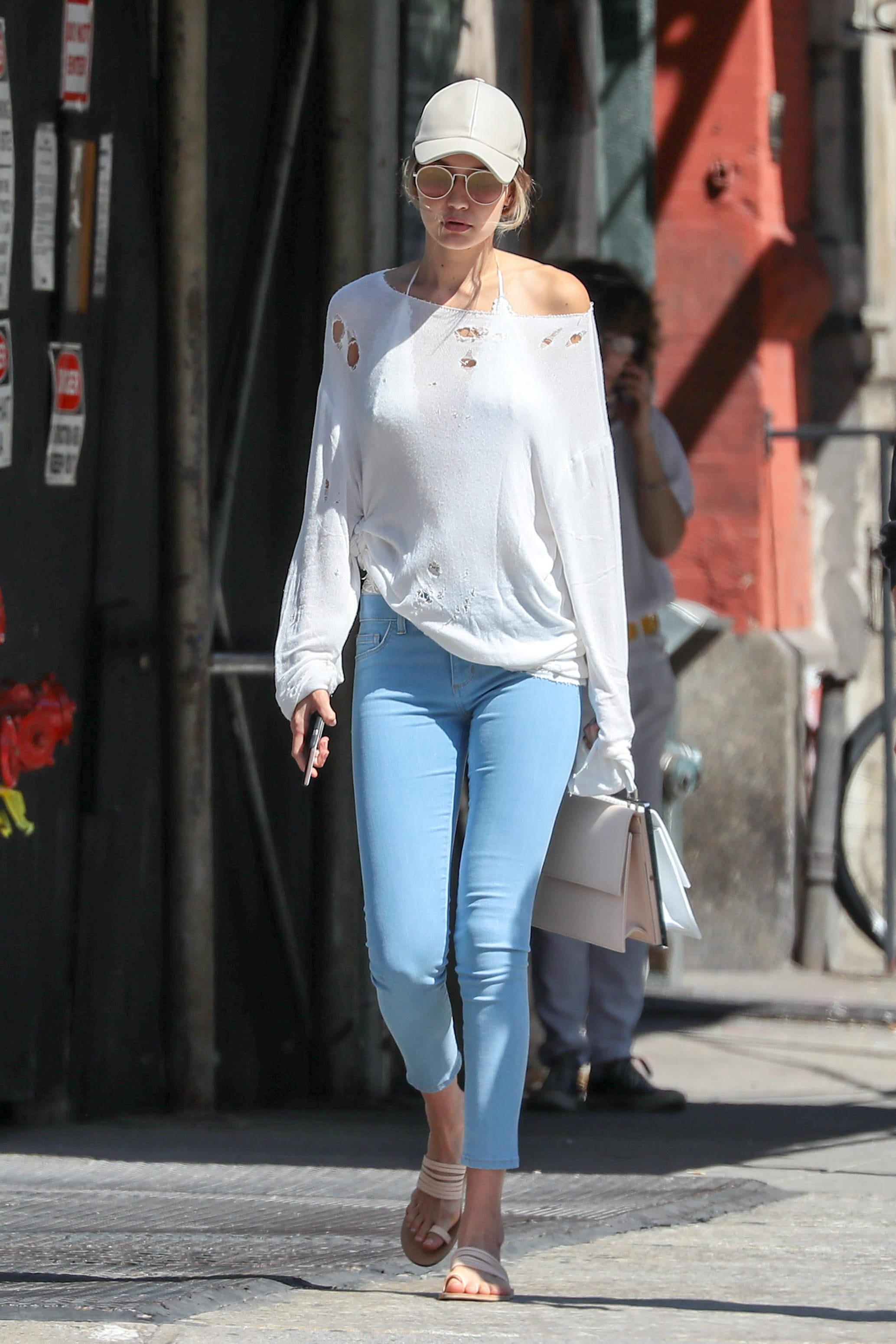 Gigi Hadid strolling through New York in her totes caj dad cap.