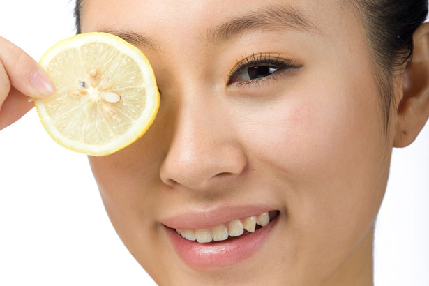 Asian model with clear skin smiling holding a lemon slice