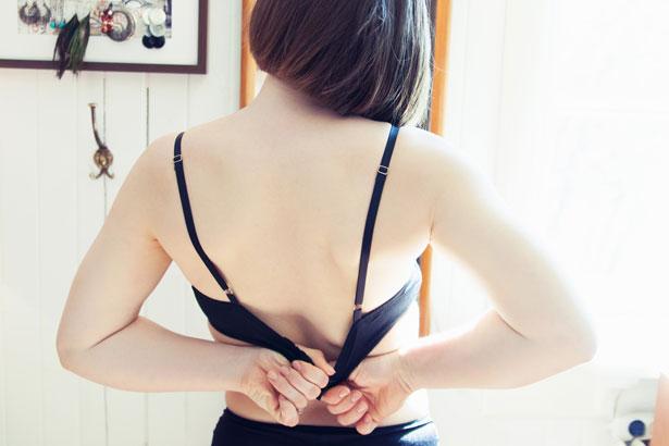 woman putting on bra