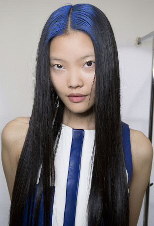 A woman with long black hair and blue roots.