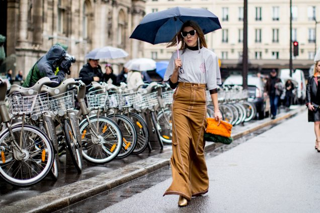 Street style: woman carrying umbrella and wearing stylish rainy day outfit